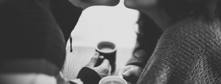 couple-kissing-over coffee